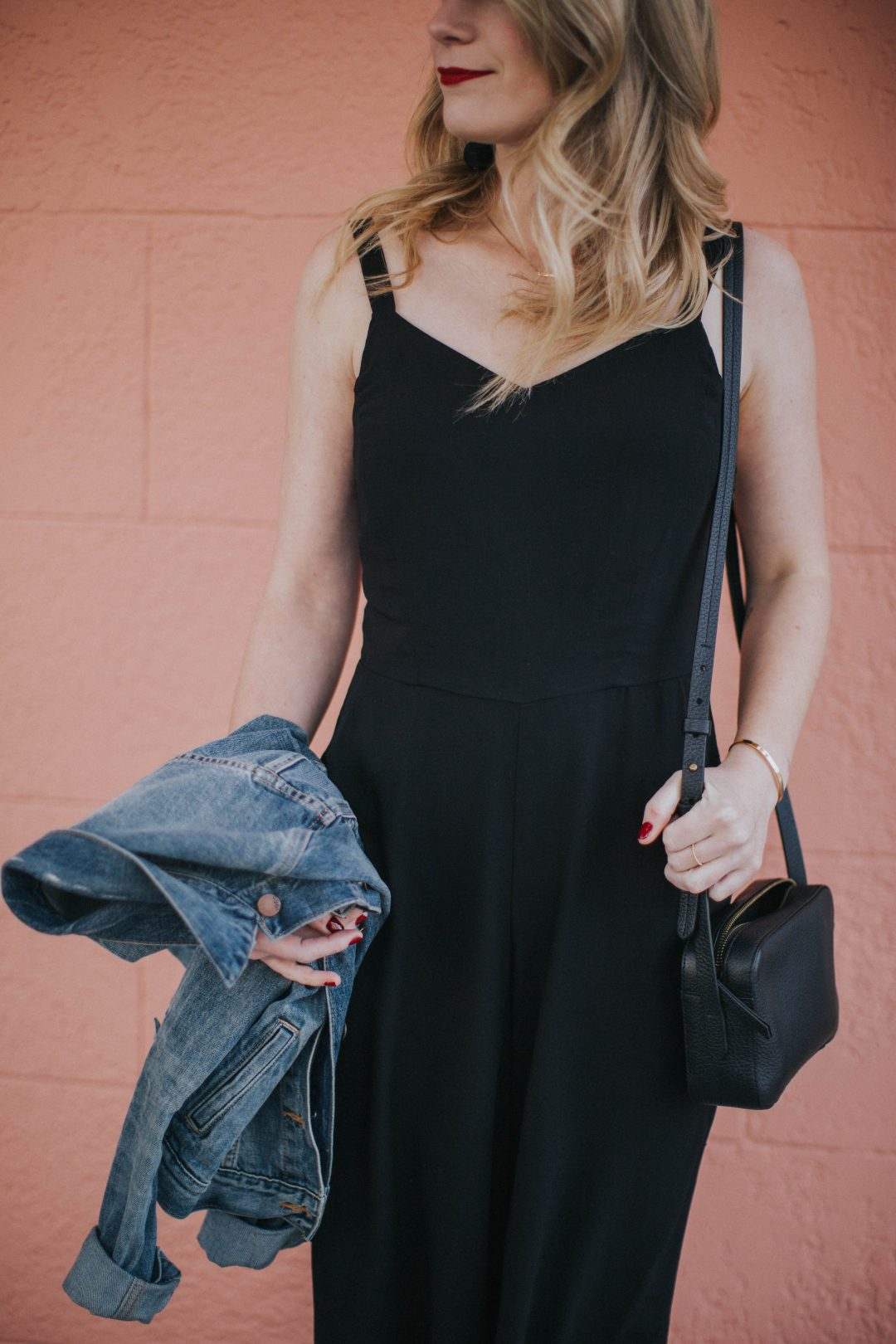 Blogger Cait Weingartner of Pretty & Fun wearing Old Navy culotte jumpsuit with M. Gemi sandals and a GAP denim jacket.
