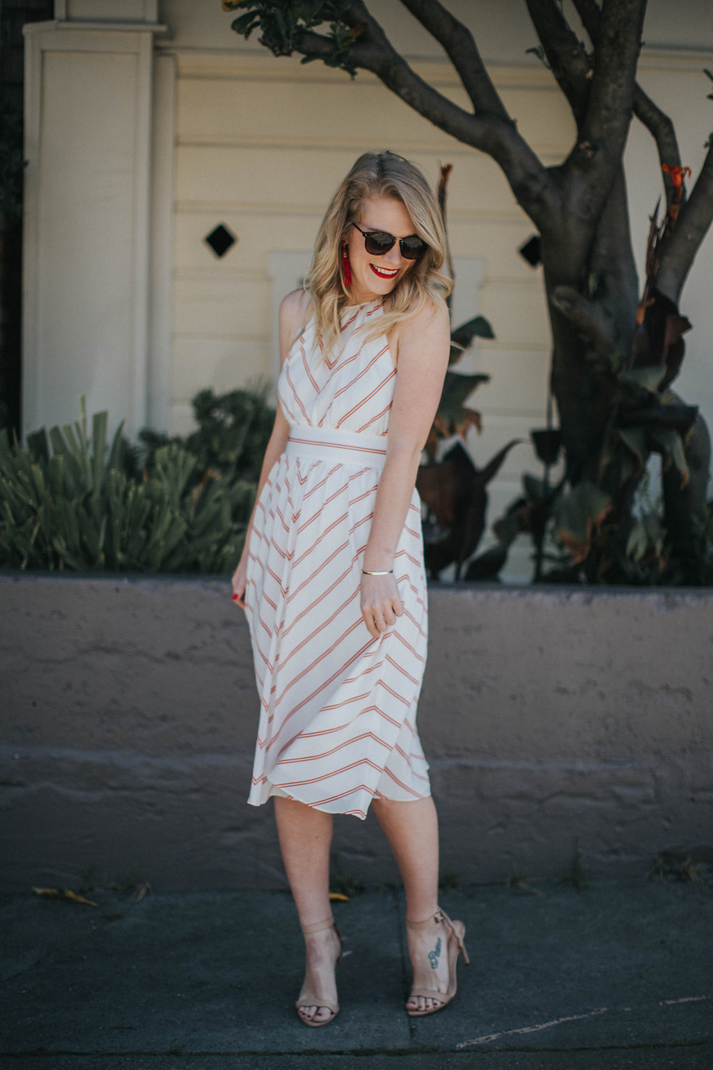Cait Weingartner wears a swingy striped Club Monaco dress with Loeffler Randall heels and BaubleBar earrings.